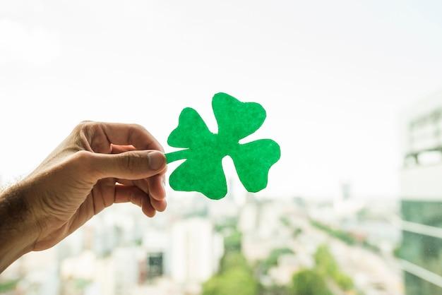 Hand, die grünbuchshamrock und ansicht des stadtbildes zeigt Kostenlose Fotos
