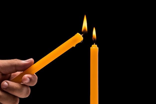 Hand, die helle brennende kerze anhält. Premium Fotos