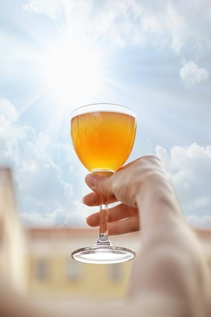 Hand, die helles cocktail vor dem himmel hält Premium Fotos
