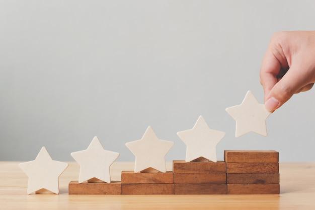 Hand, die hölzerne form mit fünf sternen auf tabelle setzt. das beste konzept für die bewertung des kundenerlebnisses durch exzellente unternehmensdienstleistungen Premium Fotos