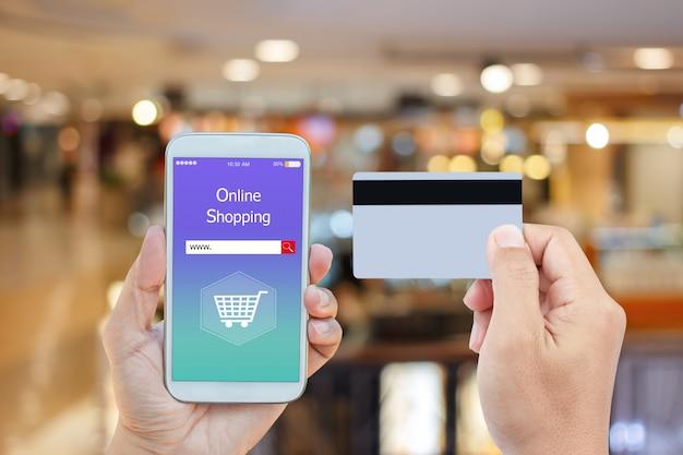 Hand, die intelligentes telefon mit dem on-line-einkaufen auf schirm und kreditkarte hält Premium Fotos