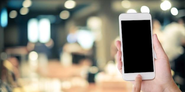 Hand, die intelligentes telefon über unschärfelestauranthintergrund hält Premium Fotos