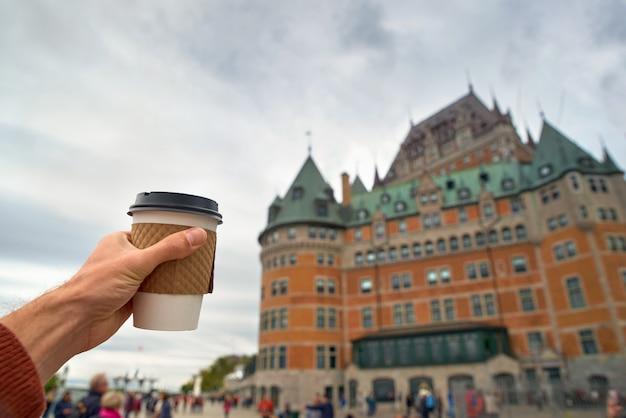 Hand, die kaffeetasse in quebec city hält. nahaufnahme und selektiver fokus Premium Fotos