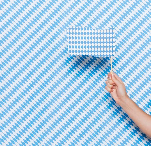 Hand, die kleine flagge mit musterhintergrund hält Kostenlose Fotos