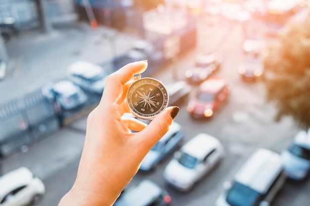 Hand, die kompaß über straße mit autos hält Kostenlose Fotos