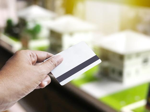 Hand, die kreditkarte über abstrakt verwischt von hausmodellproben auf regalen für immobilien- und architekturgeschäftskonzept hält. montage-stil. Premium Fotos