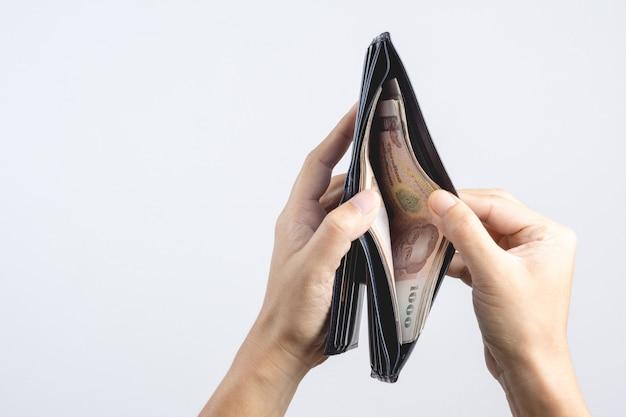 Hand, die lederne geldbörse des mannes voll mit thailändischen banknoten von 1000 baht hält Premium Fotos