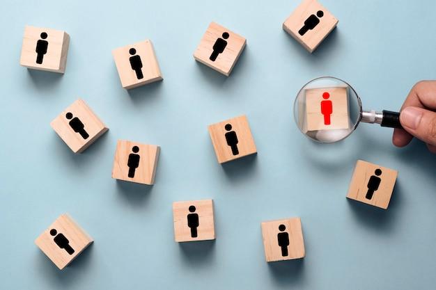 Hand, die lupe hält, um rote menschliche ikone auf hölzernem würfelblock unter schwarzer personenikone zu suchen. Premium Fotos