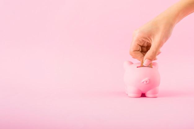 Hand, die münze in rosa sparschwein setzt Kostenlose Fotos