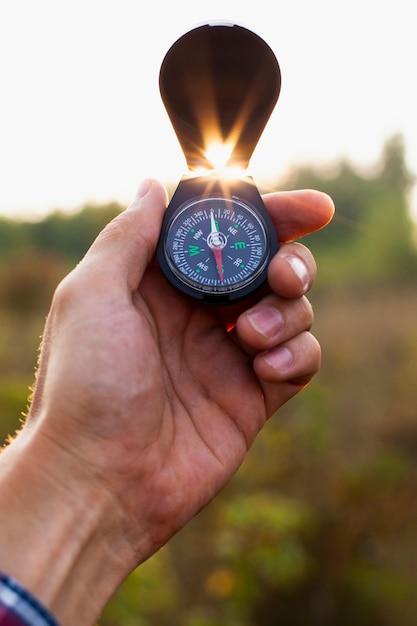 Hand, die offenen kompass in der luft hält Kostenlose Fotos