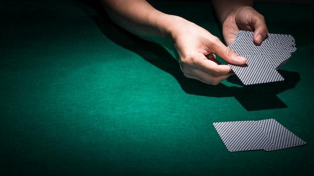 Hand, die pokerkarte auf grüner kasinotabelle hält Kostenlose Fotos