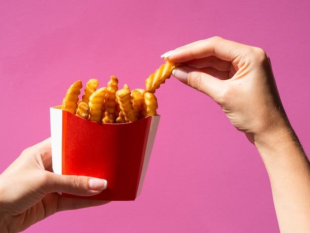 Hand, die pommes-frites auf rosa hintergrund auswählt Kostenlose Fotos