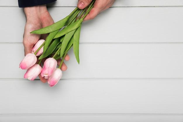 Hand, die rosa tulpenblumenstrauß hält Kostenlose Fotos