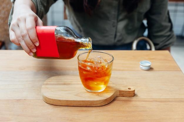 Hand, die roten aufkleber kalten gebräu-tee in trinkglas mit eis gießt. Premium Fotos