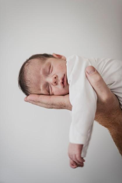 Hand, die schläfriges kleines baby hält Premium Fotos