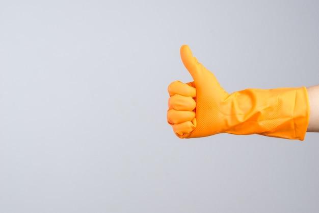 Hand, die schützenden gummihandschuh mit dem daumen herauf geste trägt Premium Fotos