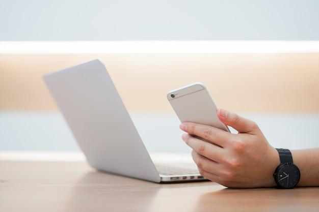 Hand, die smartphone hält und auf gerät mit laptop verwendet Premium Fotos