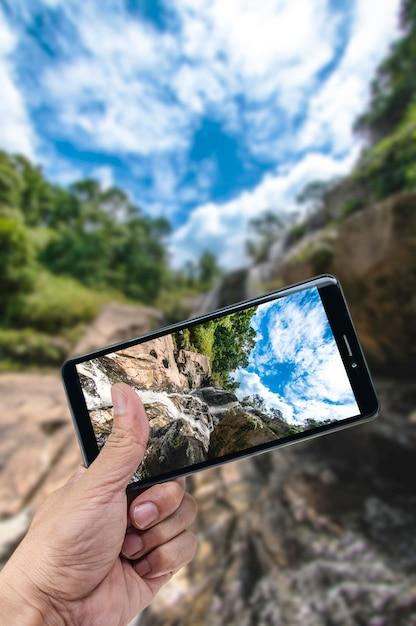 Hand, die smartphonelandschaftsnaturhintergrund hält Premium Fotos