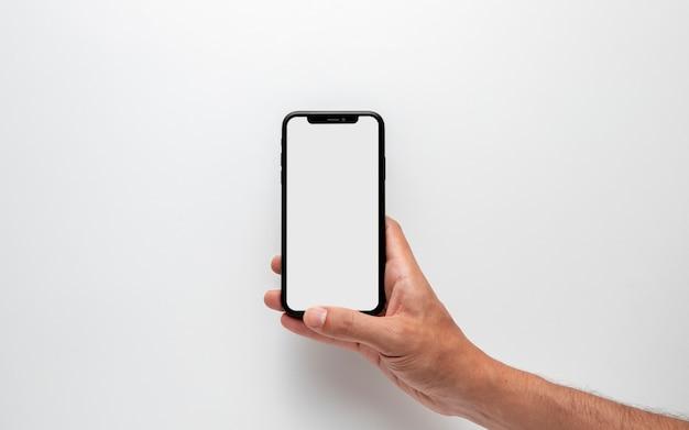Hand, die smartphonemodell hält Kostenlose Fotos