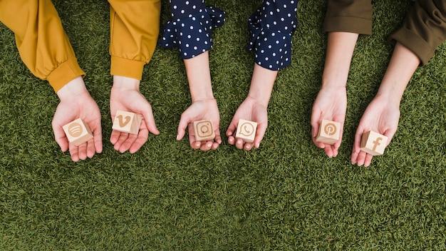Hand, die social media-app-ikonenholzklötze auf grünem gras hält Kostenlose Fotos
