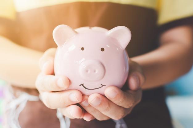 Hand, die sparschwein hält. sparen sie geld und geld Premium Fotos