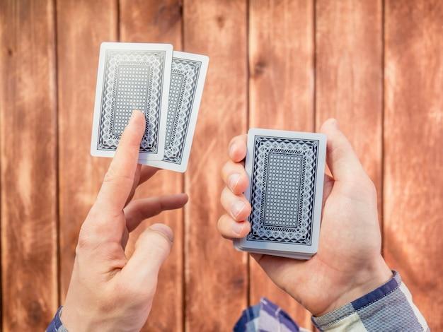 Hand, die spielkarten über der holzoberfläche mischt Premium Fotos