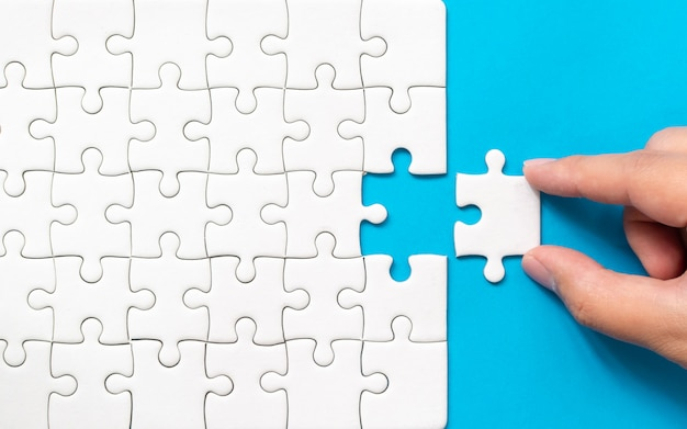 Hand, die stück weißes puzzle auf blauen hintergrund setzt Premium Fotos