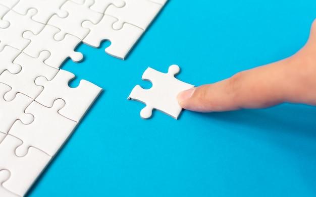 Hand, die stück weißes puzzle auf blauen hintergrund setzt. Premium Fotos