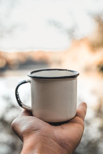 Hand, die tasse kaffee auf natürlichem hintergrund hält Premium Fotos