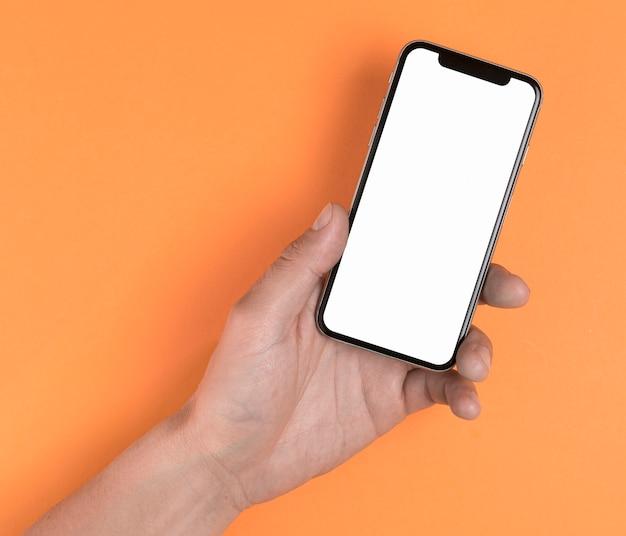 Hand, die telefon auf gelbem hintergrundspott oben hält Kostenlose Fotos