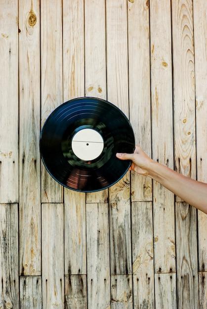 Hand, die vinylaufzeichnung über hölzernem hintergrund hält Premium Fotos