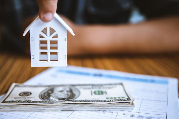 Hand, die vorbildliches weißes haus auf dollarbanknote hält. immobilienkonzept für versicherungen und immobilieninvestitionen. Premium Fotos