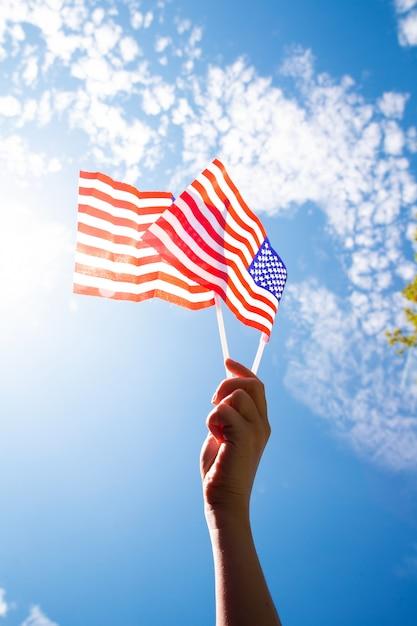 Hand, die zwei amerikanische flaggen auf dem blauen himmel mit sonnenlichthintergrund, winkende flagge für vereinigte staaten von amerika nahaufnahme hält Premium Fotos