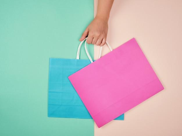 Hand, die zwei papiereinkaufstaschen auf einem pastell hält Premium Fotos