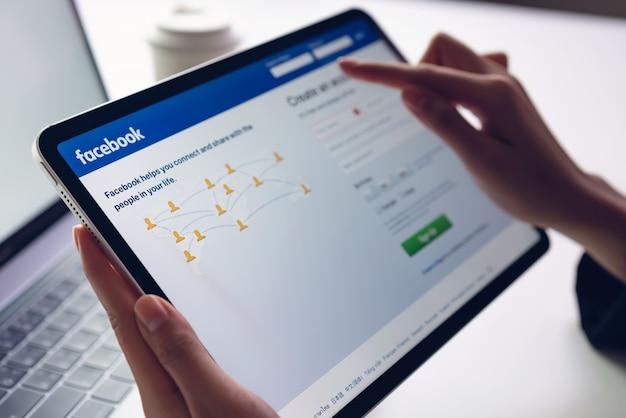 Hand drückt den facebook-bildschirm auf apple ipad pro, den social media für den informationsaustausch und das networking verwenden. Premium Fotos