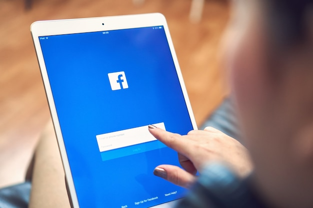 Hand drückt den facebook-bildschirm auf den tisch Premium Fotos