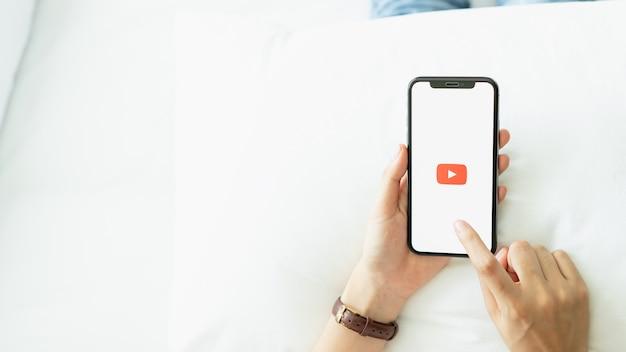 Hand drückt der bildschirm und zeigt die youtube-app-symbole auf dem apple iphone an. youtube. Premium Fotos