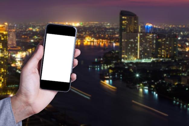 Hand ein teil des mannes halten smartphone leeren bildschirm mit stadtbild hintergrund. Premium Fotos