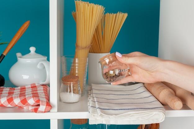 Hand einer frau, die küchengeschirr von einem küchenregal nimmt Premium Fotos