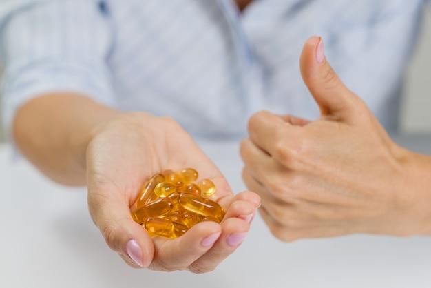 Hand einer frau mit fischöl omega-3-kapseln Premium Fotos