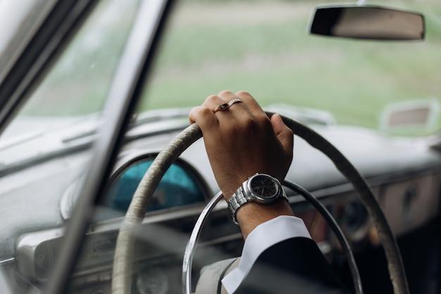 Hand eines mannes am lenkrad eines altmodischen autos, herrenuhr Kostenlose Fotos