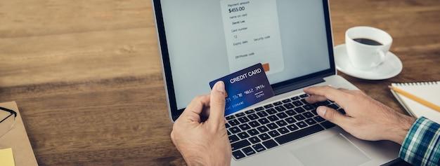 Hand eines mannes, der kreditkarte online, zur zahlung mit laptop-computer hält Premium Fotos