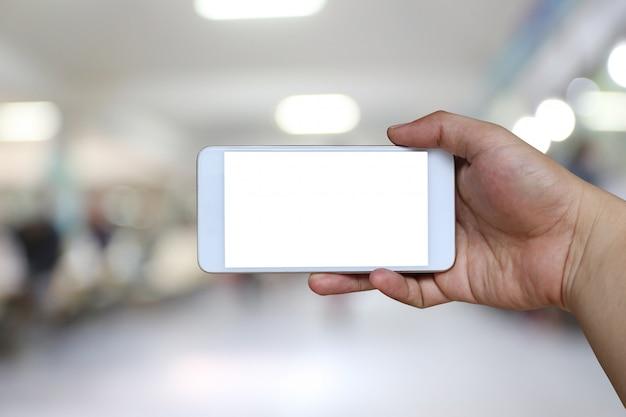 Hand eines mannes, der smartphonegerät auf unschärfekrankenhaus hält. Premium Fotos