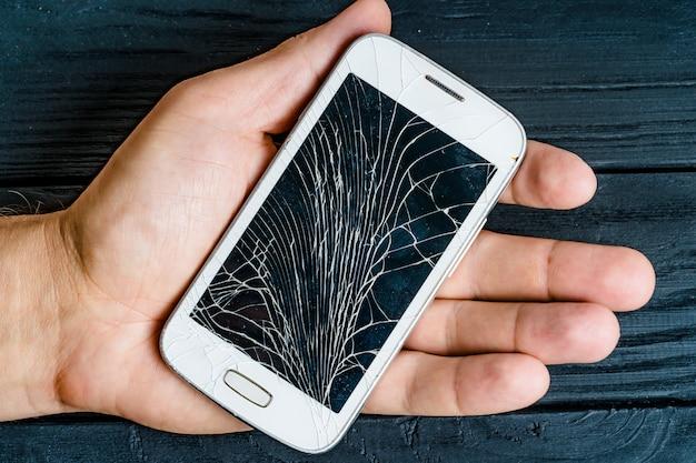 Hand eines mannes, der zuhause weißen smartphone mit schädigendem glasschirm hält. Premium Fotos