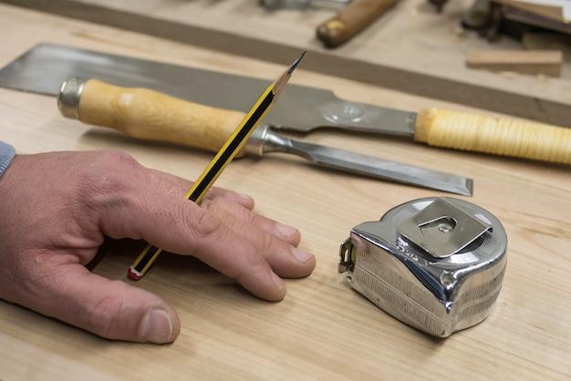 Hand eines tischlers mit einem bleistift Premium Fotos