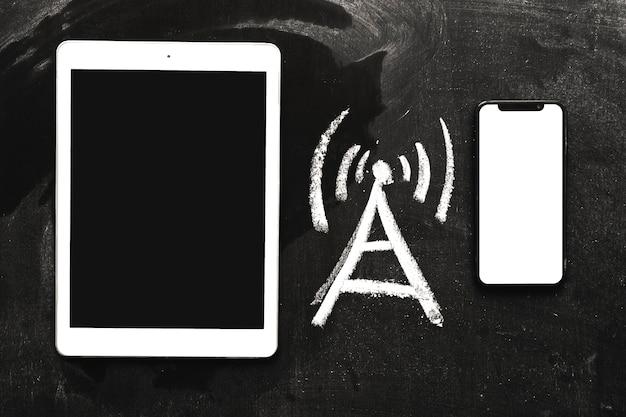 Hand gezeichnete netzsignalikone zwischen der digitalen tablette und dem mobiltelefon auf tafel Kostenlose Fotos