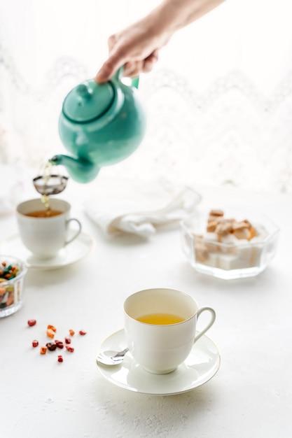 Hand gießt tee in teetassen Premium Fotos