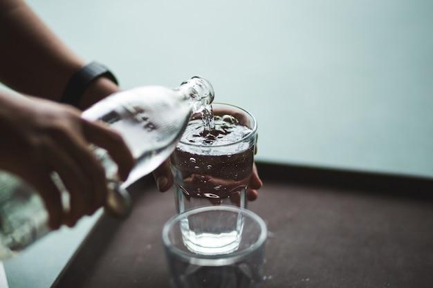 Hand gießt wasser in eine glasflasche Premium Fotos