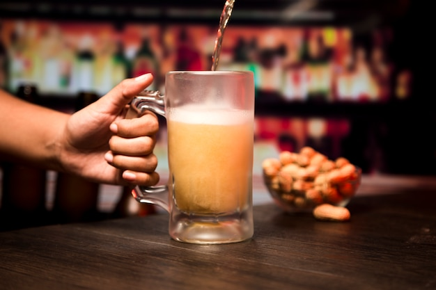 Hand hält bierglas Kostenlose Fotos