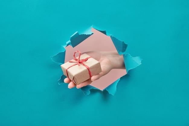 Hand hält ein bastelgeschenk durch ein zerrissenes papierloch Premium Fotos